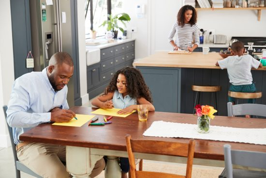 Young black family busy in their kitchen, elevated view